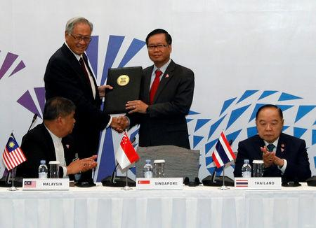 Singapore's Defence Minister Ng Eng Hen presents a signed joint declaration to ASEAN Deputy Secretary General Hoang Anh Tuan at the ASEAN Defence Ministers&#x27 Meeting in Singapore