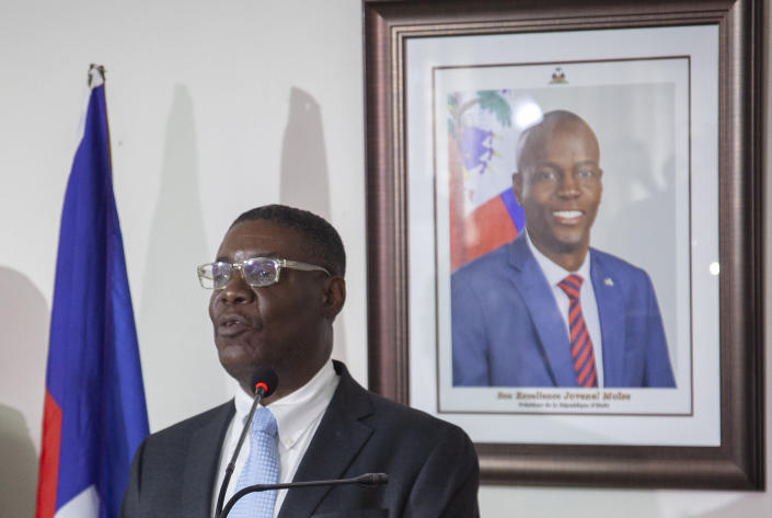 Haiti's newly-named Justice Minister Liszt Quitel, speaks during his installation ceremony, backdropped by a photo of assassinated President Jovenel Moise, in Port-au-Prince, Haiti, Thursday, Sept. 16, 2021. (AP Photo/Richard Pierrin)