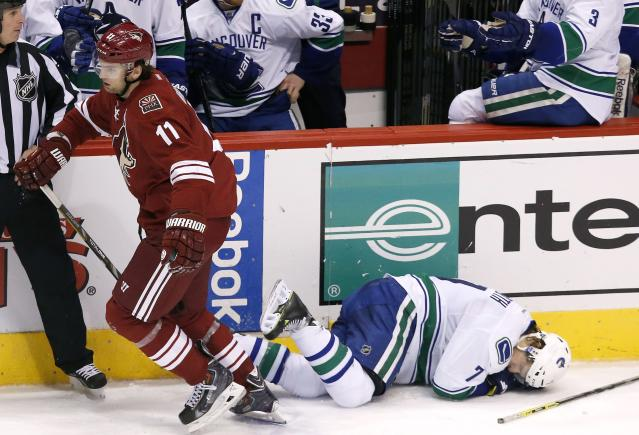 Phoenix Coyotes' Martin Hanzal (11), of the Czech Republic, skates away after knocking Vancouver Canucks' David Booth (7) to the ice, but earned a four-minute high-sticking penalty on the play, during the third period of an NHL hockey game Thursday, Jan. 16, 2014, in Glendale, Ariz. The Coyotes defeated the Canucks 1-0. (AP Photo/Ross D. Franklin)