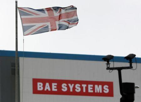 FILE PHOTO: A union flag flies over the entrance to the naval dockyards, where BAE Systems are also located, in Portsmouth