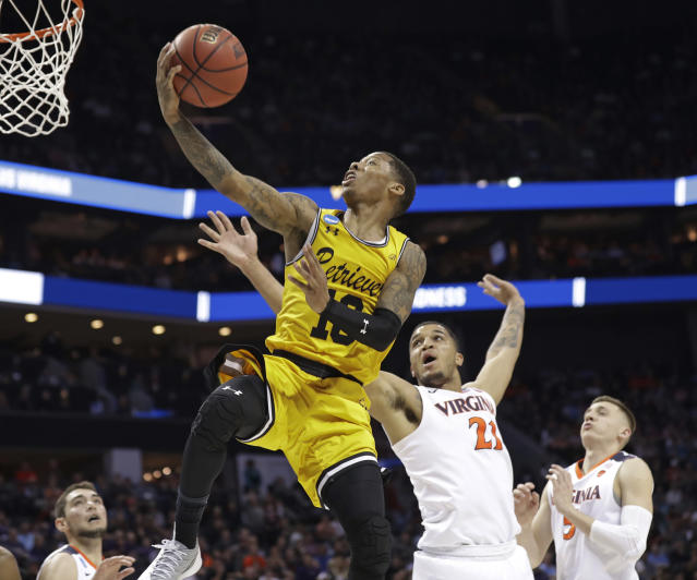 UMBC's Jairus Lyles (10) drives past Virginia's Isaiah Wilkins (21) and Kyle Guy (5) during the second half of a first-round game in the NCAA men's college basketball tournament in Charlotte, N.C., Friday, March 16, 2018. (AP Photo/Gerry Broome)