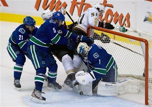 Vancouver Canucks' goalie Roberto Luongo, right, makes the save as teammates Mason Raymond (21) and Jason Garrison (5) check Anaheim Ducks' Corey Perry (obscured) and Kyle Palmieri (51) during the third period of an NHL hockey game in Vancouver, British Columbia, on Saturday, Jan. 19, 2013. (AP Photo/The Canadian Press, Darryl Dyck)