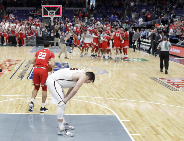 Loyola of Chicago's Cameron Krutwig bends over in the foreground as members of Bradley celebrate their victory in the background following an NCAA college basketball game in the semifinal round of the Missouri Valley Conference tournament, Saturday, March 9, 2019, in St. Louis. (AP Photo/Jeff Roberson)