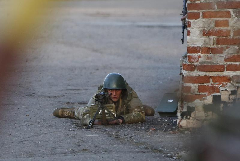 An Ukrainian soldier aims his weapon at pro-Russia protesters gathered in front of an Ukrainian airbase in Kramatorsk