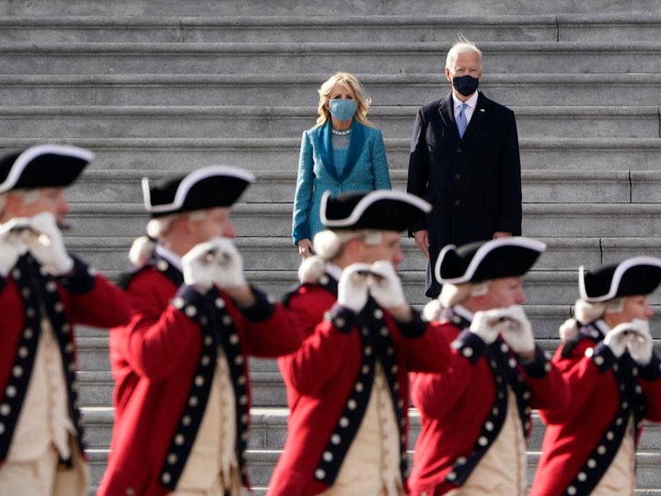 Joe Biden and his wife Jill Biden watch a military pass in review ceremony on the East Front of the Capitol at the conclusion of the inauguration ceremoniesAP