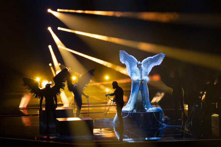 In this photo taken on May 12, 2021, a man untangles the chains as Norway's Tix rehearses his song Fallen Angel at the Eurovision Song Contest at Ahoy arena in Rotterdam, Netherlands. After last year's Eurovision Song Contest was canceled amid the global COVID-19 pandemic, it is roaring back to life with coronavirus bubbles added to its heady mix of music and camp. Bands and singers from 39 countries are competing in the Dutch port city of Rotterdam for the coveted title that can be a springboard to a global career or a fleeting taste of flame. (AP Photo/Peter Dejong)