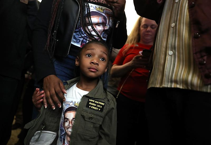 A young girl wears a shirt with an image of Stephon Clark.