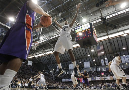 Butler forward Kameron Woods, center, defends an inbound throw by Evansville guard Troy Taylor during the second half of an NCAA college basketball game, Saturday, Dec. 22, 2012, in Indianapolis. Butler won 75-67. (AP Photo/AJ Mast)
