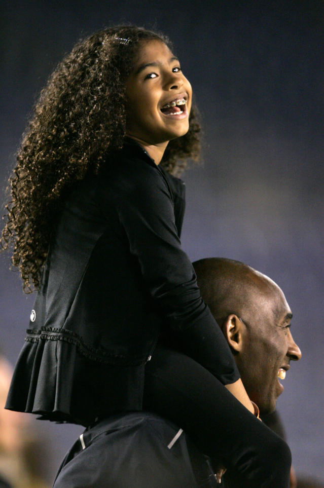 Kobe Bryant stands on the sideline with his daughter Gianna Maria-Onore Bryant on his shoulders prior to the start of the game against the United States and China during an international firendly match at Qualcomm Stadium on April 10, 2014 in San Diego, California. (Photo by Kent C. Horner/Getty Images)