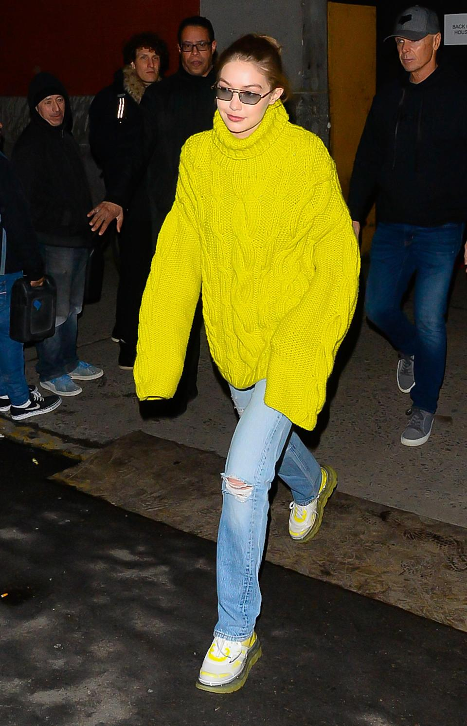 A girl's gotta stay cozy — and match her footwear while doing it! Coming off the tail end of the tiny sunglasses trend, Gigi stepped out in a mega-long sleeved electric yellow cable-knit turtleneck. The perfect accessories for sweater days? Jeans and sneaks, obvi.