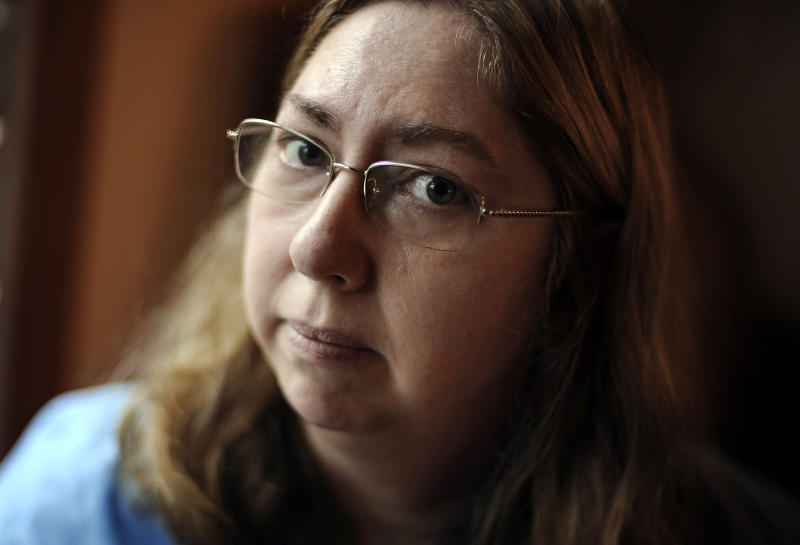 In this Monday, Dec. 23, 2013 photo, Leslie Lynch poses for a photograph in her home in Glastonbury, Conn. Lynch, who lost her job last year, is moving out of her home of 21 years because she can no longer afford the mortgage payments. (AP Photo/Jessica Hill)