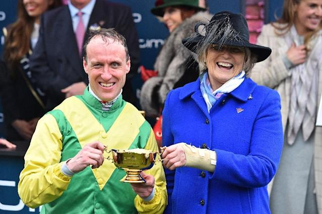 Jockey Robbie Power (L) and Irish trainer Jessica Harrington celebrate after winning the Gold Cup with their runner Sizing John on the final day of the Cheltenham Festival horse racing meeting at Cheltenham Racecourse in Gloucestershire, south-west England, on March 17, 2017. (AFP Photo/Glyn KIRK )