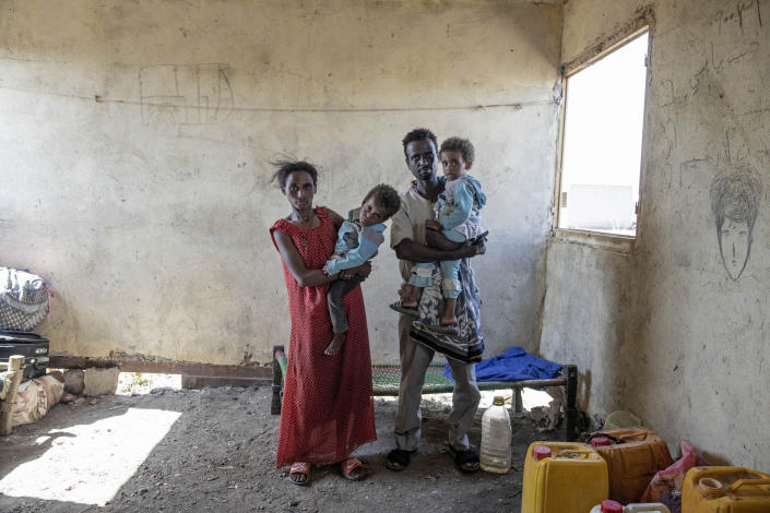"""Tesfaalem Germay, 34, an ethnic Tigrayan survivor from Mai-Kadra, Ethiopia, poses for a photograph with his wife Bethlehem, 21, and their twin daughters inside a temporary shelter at Village 8, the transit center near the Lugdi border crossing, eastern Sudan, Nov. 22, 2020. Witnesses say hundreds of civilians were slaughtered in Mai-Kadra, but they disagree about who killed whom. """"Anyone they found, they would kill,"""" Germay said of Ethiopian federal and Amhara regional forces. Others say it was Tigrayan forces and their allies who were responsible. (AP Photo/Nariman El-Mofty)"""