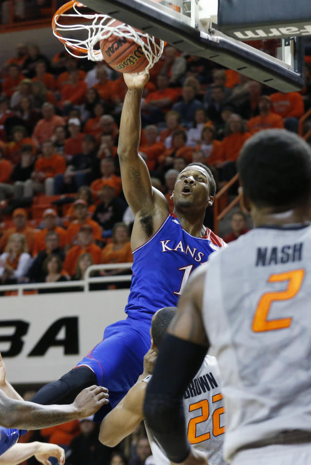 Kansas guard Wayne Selden Jr. (1) dunks over Oklahoma State wing Markel Brown (22) in the first half of an NCAA college basketball game in Stillwater, Okla., Saturday, March 1, 2014. (AP Photo/Sue Ogrocki)