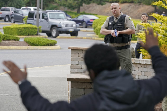 Kevin Burton-Crow, right, of the Thurston Co. Sheriff's Dept., points a training gun at Naseem Coaxum, an actor playing the role of a person causing a disturbance at a convenience store, during a training class at the Washington state Criminal Justice Training Commission, Wednesday, July 14, 2021, in Burien, Wash. Washington state is embarking on a massive experiment in police reform and accountability following the racial justice protests that erupted after George Floyd's murder last year, with nearly a dozen new laws that took effect Sunday, July 25, but law enforcement officials remain uncertain about what they require in how officers might respond — or not respond — to certain situations, including active crime scenes and mental health crises. (AP Photo/Ted S. Warren)