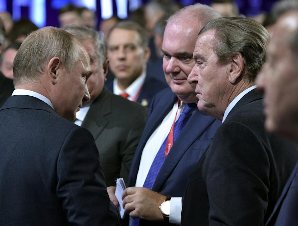 Russian President Vladimir Putin and former German Chancellor Gerhard Schroeder stand facing each other among a group of others.
