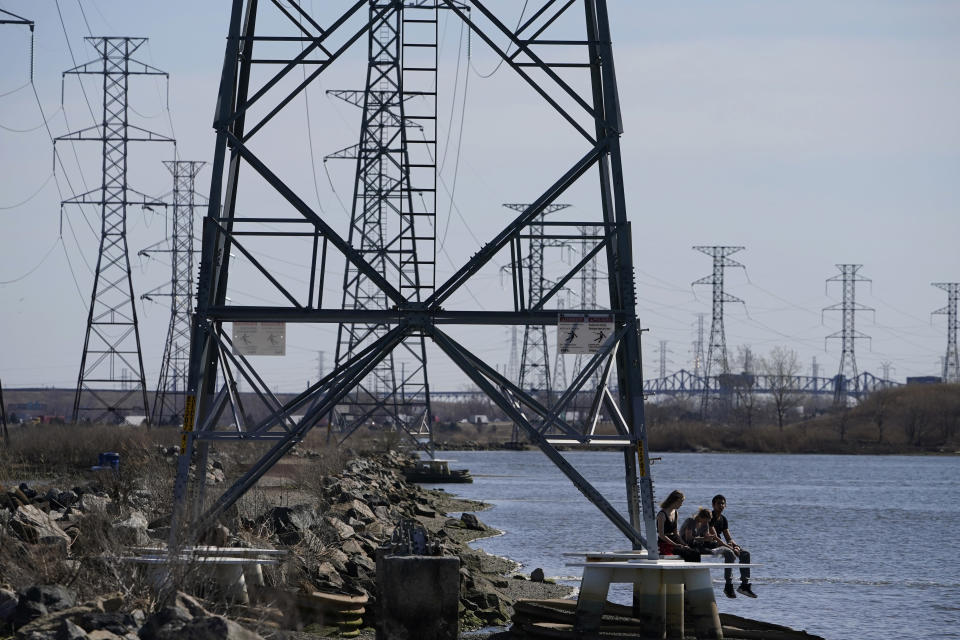 "People sit at the base of a transmission tower in North Arlington, N.J., Tuesday, April 6, 2021. President Joe Biden is setting about convincing America it needs his $2.3 trillion infrastructure plan, deputizing a five-member ""jobs Cabinet"" to help in the effort. But the enormity of his task is clear after Senate Minority Leader Mitch McConnell's vowed to oppose the plan ""every step of the way."" (AP Photo/Seth Wenig)"