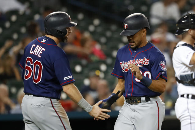 Minnesota Twins' Jake Cave (60) and LaMonte Wade Jr. (30) celebrate scoring in the seventh inning of a baseball game against the Detroit Tigers in Detroit, Tuesday, Sept. 24, 2019. (AP Photo/Paul Sancya)