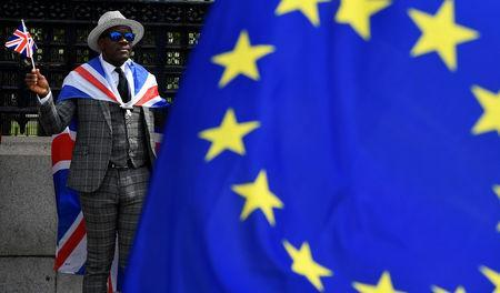 FILE PHOTO: A pro-Brexit protester stands behind an EU flag ahead of the forthcoming EU elections, outside of the Houses of Parliament in London, Britain, May 22, 2019. REUTERS/Toby Melville/File Photo