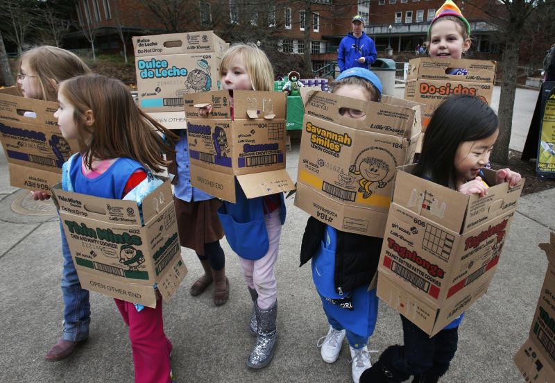 FILE - In a Feb. 18, 2013 file photo dressed in boxes emptied from earlier cookie sales, Girl Scouts from Troop 20337 in Eugene fan out on the University of Oregon campus near the Erb Memorial Union in Eugene, Ore., in search of customers for their cookies. Just a year after its 2012 centennial celebrations, the Girl Scouts of the USA's interconnected problems include declining membership and revenues, a dearth of volunteers, rifts between leadership and grass-roots members, a pension plan with a $347 million deficit, and an uproar over efforts by many local councils to sell venerable summer camps. (AP Photo/The Register-Guard, Chris Pietsch)