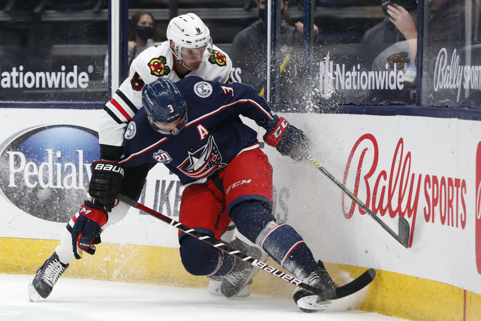 Chicago Blackhawks' Dominik Kubalik, left, and Columbus Blue Jackets' Seth Jones fight for the puck during the first period of an NHL hockey game Saturday, April 10, 2021, in Columbus, Ohio. (AP Photo/Jay LaPrete)