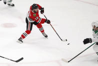 Chicago Blackhawks left wing Alex DeBrincat (12) shoots the puck for a goal against the Dallas Stars during the second period of an NHL hockey game Tuesday, April 6, 2021, in Chicago. (AP Photo/Jeff Haynes)