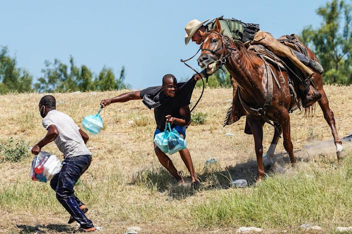 A border patrol agent on horseback tries to stop a Haitian migrant from entering an encampment on the banks of the Rio Grande near the Acuna Del Rio International Bridge in Del Rio, Texas, on Sept. 19, 2021. (Paul Ratje / AFP - Getty Images)