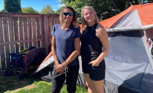 David McDonald, left, and Kim Cormier have become fast friends ever since Cormier invited McDonald to pitch his tent in the backyard of her Kingston, Ont., home. Next month, they're hoping to take delivery of McDonald's new micro home. (Andrew Embury - image credit)