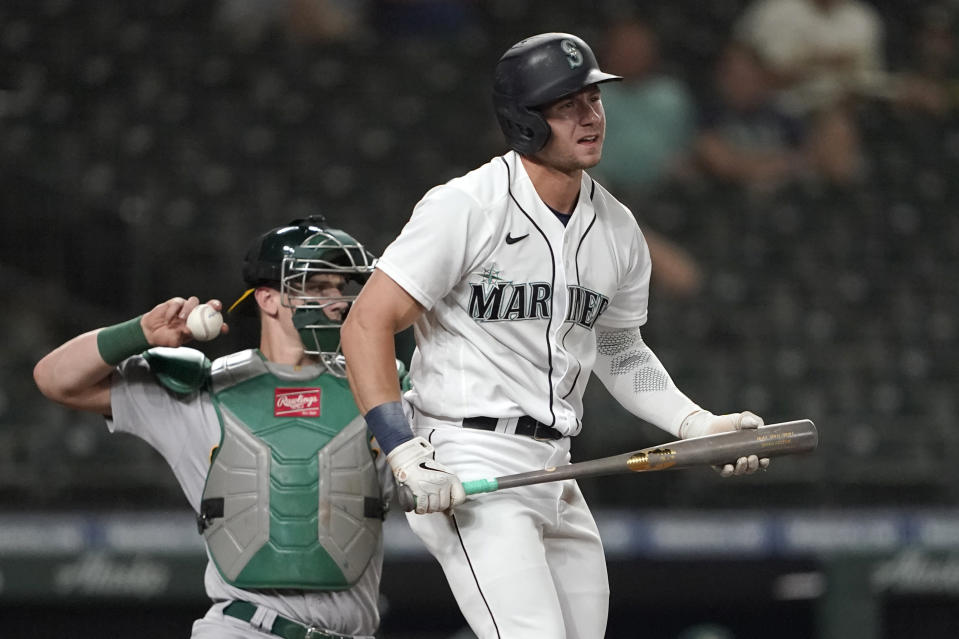 Seattle Mariners' Jarred Kelenic reacts after striking out swinging, while Oakland Athletics catcher Sean Murphy returns the ball during the eighth inning of a baseball game Tuesday, June 1, 2021, in Seattle. (AP Photo/Ted S. Warren)