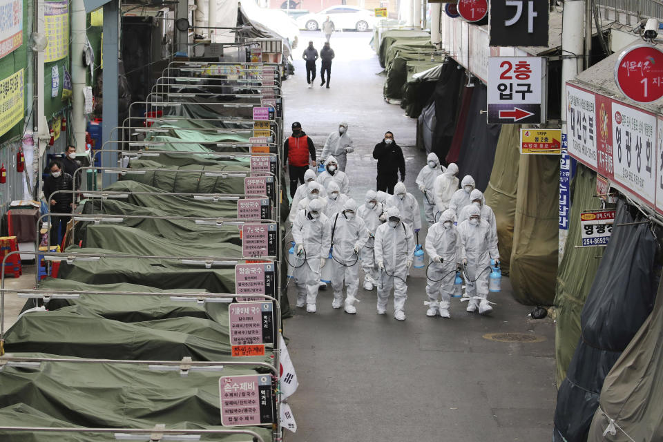 """Workers wearing protective gear spray disinfectant as a precaution against the COVID-19 coronavirus in a local market in Daegu, South Korea, Sunday, Feb. 23, 2020. South Korea's president has put the country on its highest alert for infectious diseases and says officials should take """"unprecedented, powerful"""" steps to fight a viral outbreak. (Im Hwa-young/Yonhap via AP)"""