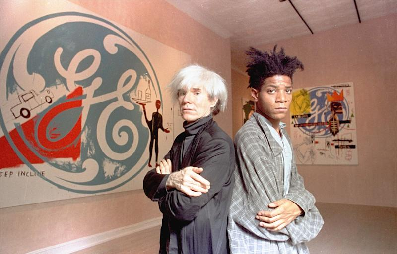Andy Warhol and Jean-Michel Basquiat in front of their collaborative paintings at the Tony Shafrazi Gallery in SoHo in 1985. (Photo: Richard Drew/AP)