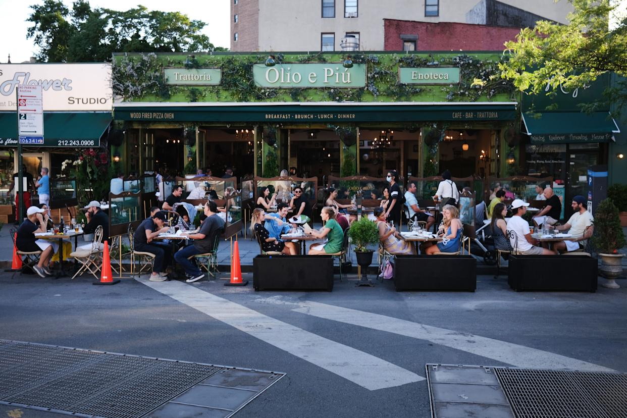 People eat and drink at tables placed outside of a Manhattan restaurant as the city enters Phase 2 of re-opening following restrictions imposed to curb the coronavirus pandemic on June 24, 2020.