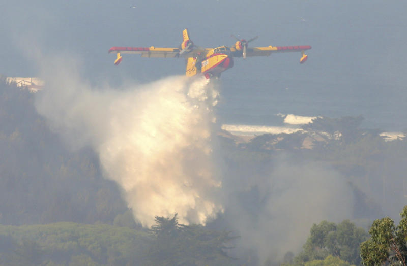 A firefighting airplane drops its load, with Guincho beach in the background, outside the village of Charneca, in the Sintra national park, west of Lisbon, Sunday, Oct. 7, 2018. Over 700 firefighters were battling a forest fire that started overnight about 40 kilometers (25 miles) west of Lisbon. (AP Photo/Armando Franca)