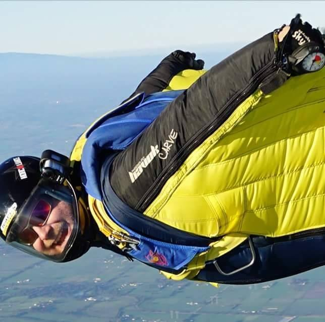 A close up photos of Arron Toepfer skydiving showing him looking at the camera smiling.