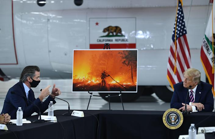 President Donald Trump speaks to California Governor Gavin Newsom at Sacramento McClellan Airport on September 14, 2020 during a briefing on wildfires. / Credit: BRENDAN SMIALOWSKI/AFP via Getty Images