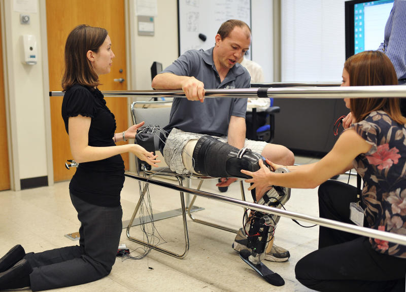 """In this Oct. 25, 2012 photo, biomedical engineer Annie Simon, left, and research prosthetist Elizabeth Halsne fit an experimental """"bionic"""" prosthetic leg on Zac Vawter at the Rehabilitation Institute of Chicago. After losing his right leg in a motorcycle accident, the 31-year-old software engineer signed up to become a research subject, helping test a trailblazing prosthetic leg that's controlled by his thoughts. He will put this leg to the ultimate test Sunday, Nov. 4 when he attempts to climb 103 flights of stairs to the top of Chicago's Willis Tower, one of the world's tallest skyscrapers. (AP Photo/Brian Kersey)"""