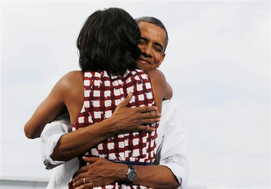 U.S. President Barack Obama hugs first lady, Michelle Obama, after she introduces him at a campaign event at the Village of East Davenport in Davenport, Iowa, August 15, 2012.