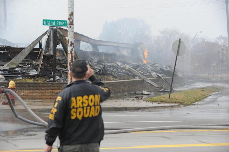 An arson investigator photographs flames and smoke from the Park Medical Plaza office building in Detroit on Tuesday, April 9, 2013 after shots were fired inside the complex and the structure was set on fire. A man believed responsible for the shooting and a woman who worked at the Park Medical Centers had not been located, said Dwane Blackmon, Detroit police homicide inspector. (AP Photo/The Detroit News, Max Ortiz) DETROIT FREE PRESS OUT. HUFFINGTON POST OUT