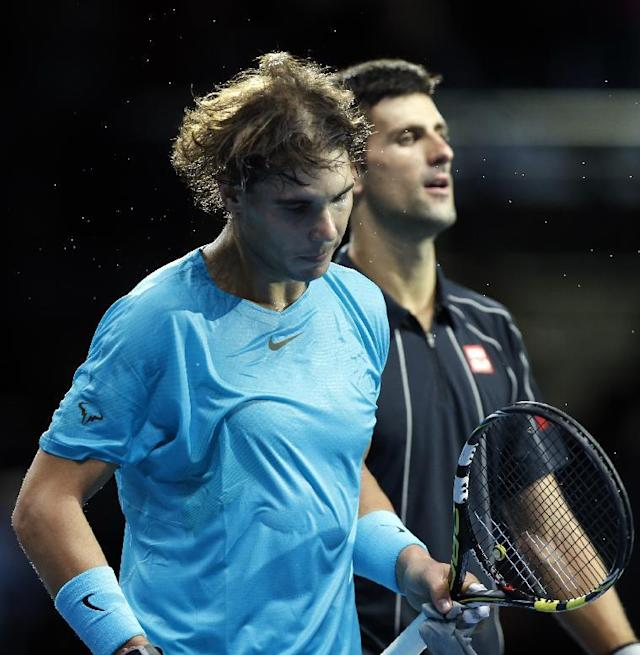 Rafael Nadal of Spain shakes his head of perspiration after Novak Djokovic of Serbia, right, wins the final of the ATP World Tour Finals single tennis match at the O2 Arena in London Monday, Nov. 11, 2013. (AP Photo/Sang Tan)