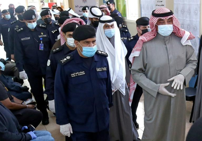 Kuwaiti Prime Minister Sheikh Sabah al-Khaled al-Sabah (R) arrives to cast his votes at a polling station in Kuwait City during parliamentary elections on December 5, 2020