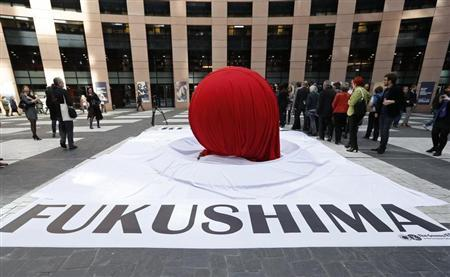 "A banner that reads ""Fukushima"" is placed in front of a giant symbolic Japan's national flag to mark the third year anniversary of the March 11, 2011 earthquake and tsunami, at the European Parliament in Strasbourg"