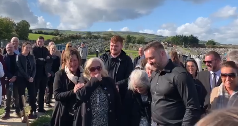 Bradley's family laugh as they hear him prank them for one last time, from beyond the grave. — Screen capture via Facebook/Andrea Bradley