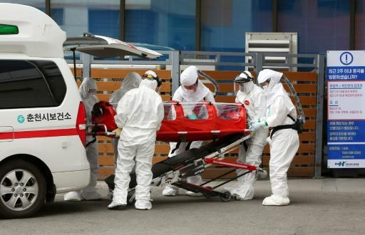 Medics carry a patient infected with coronavirus to hospital in Chuncheon