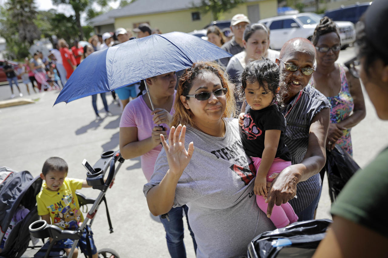 People stand in a line for water, food and supplies at a distribution point in Port Arthur, Texas, Monday, Sept. 25, 2017. Jefferson County was drowned by more than 60 inches of rain during Hurricane Harvey, the most rainfall ever recorded in a single storm in the nation's history, according to preliminary data from the National Weather Service. (AP Photo/David Goldman)