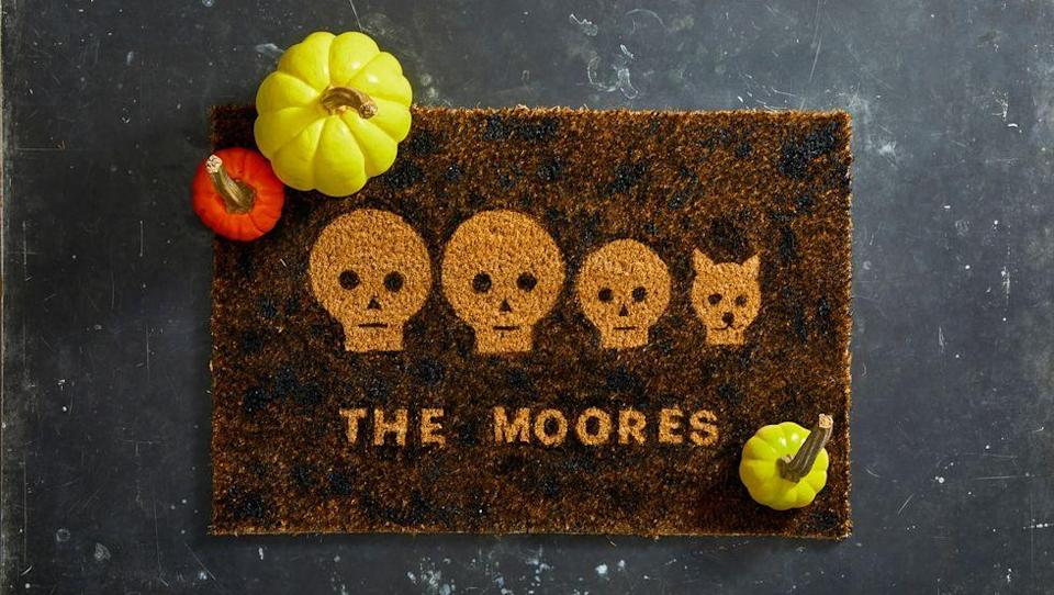 """<p>There's nothing like a festive doormat to excite trick-or-treaters. <a href=""""https://hmg-prod.s3.amazonaws.com/files/ghkhalloween-doormatstencils-1564426473.pdf?tag=syn-yahoo-20&ascsubtag=%5Bartid%7C10055.g.4602%5Bsrc%7Cyahoo-us"""" rel=""""nofollow noopener"""" target=""""_blank"""" data-ylk=""""slk:Download this skull family template"""" class=""""link rapid-noclick-resp""""><strong>Download this skull family template</strong></a> to update yours. Print out as many faces as you have people in your household. Use an X-Acto knife or craft knife to cut out faces, eyes, noses, and mouths. Then, arrange the faces on your mat. Feel free to add cut-out letters, too. Attach paper to the doormat with folded-up painter's tape on the back. Then, starting with a little paint at a time, dab paint around the stencil with a foam brush. Continue until the entire mat is covered, and let it dry completely before removing the stencils.</p>"""
