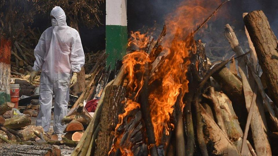 A Family member, wearing a Personal Protective Equipment (PPE), performs the last rites for COVID-19 victims at a cremation ground in Delhi, India, 29 April 2021.