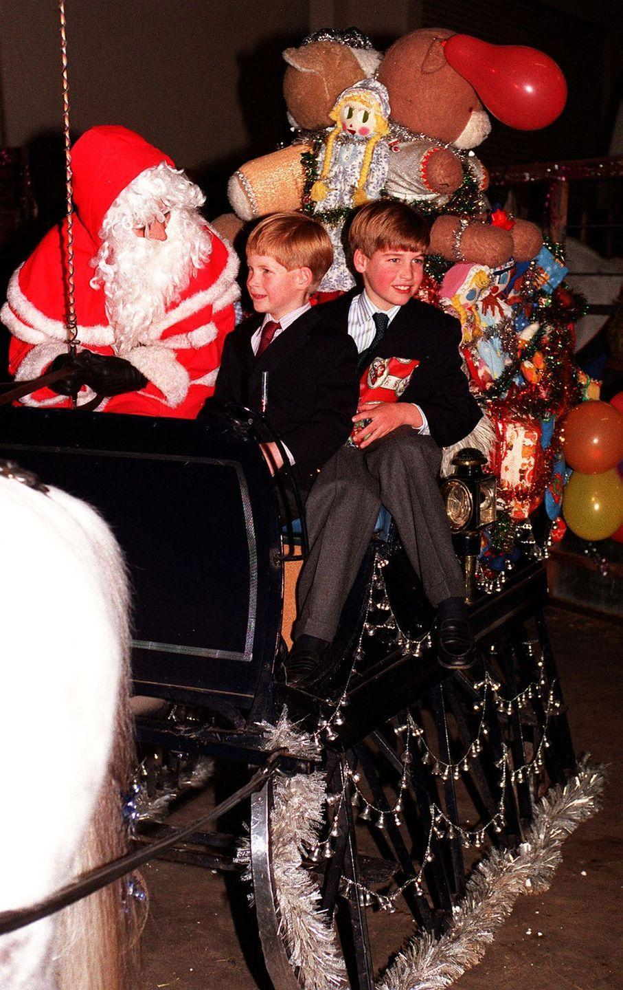 <p>Prince Harry and Prince William sit in a horse-drawn carriage with Santa.</p>