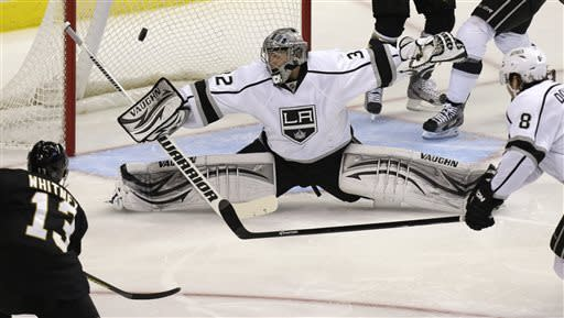 Los Angeles Kings goalie Jonathan Quick (32) stretches to block a shot as teammate Drew Doughty (8) and Dallas Stars left wing Ray Whitney (13) watch during the first period of an NHL hockey game Tuesday, April 9, 2013, in Dallas. (AP Photo/LM Otero)