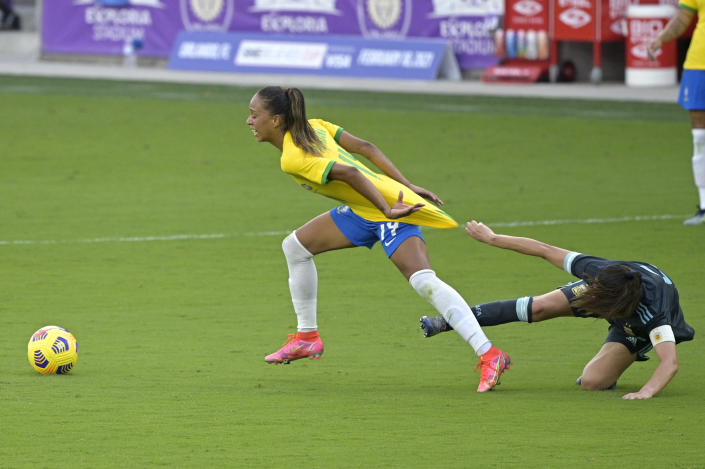 Brazil midfielder Adriana, left, is grabbed by Argentina midfielder Vanesa Santana during the second half of a SheBelieves Cup women's soccer match, Thursday, Feb. 18, 2021, in Orlando, Fla. (AP Photo/Phelan M. Ebenhack)