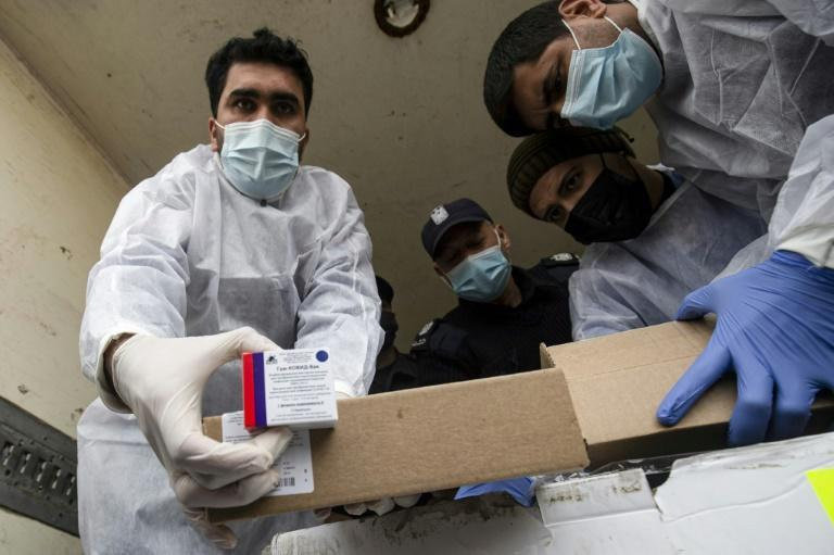 Health workers in Hamas-run Gaza unload a first consignment of coronavirus vaccines supplied by the Palestinian Authority for frontline staff after Israel relents on allowing it through its blockade